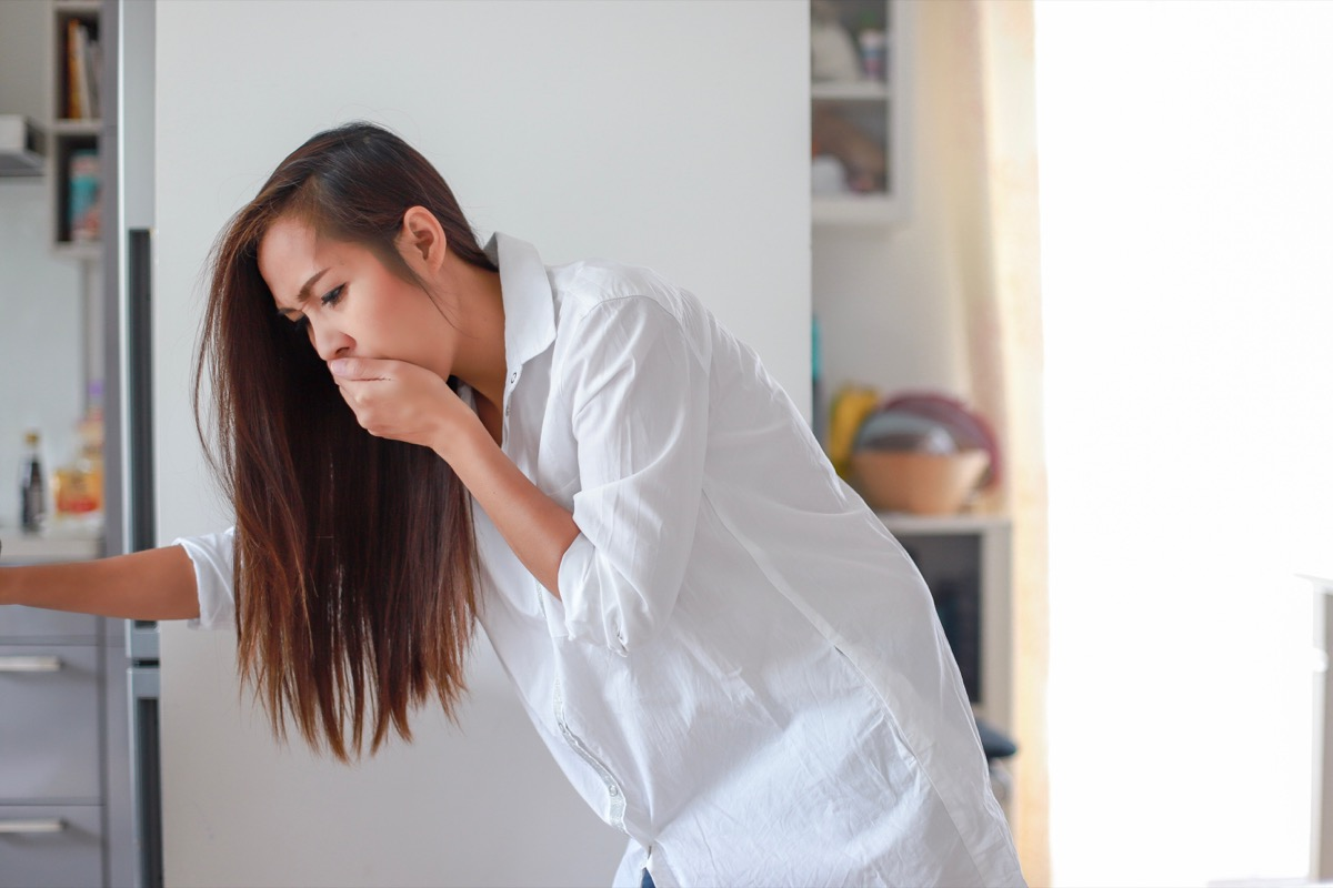 young woman with nausea covering her mouth
