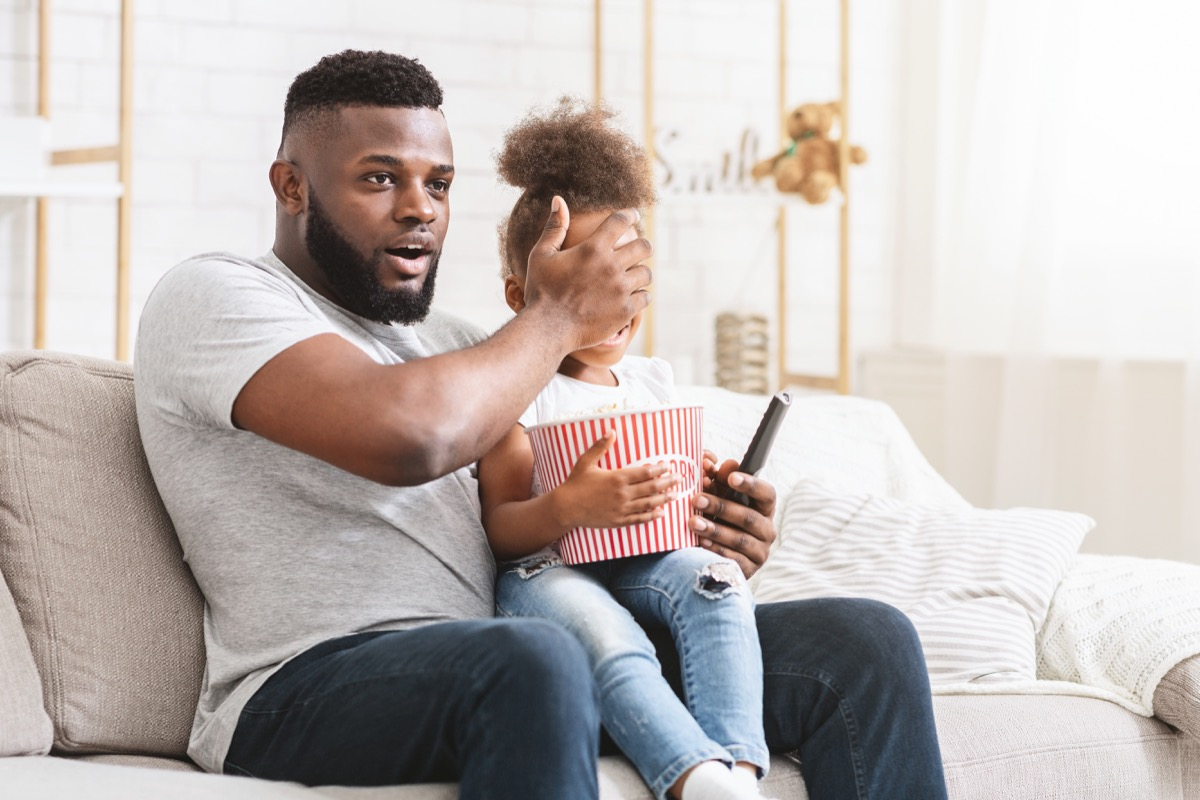 young father covering daughter's eyes while watching movie