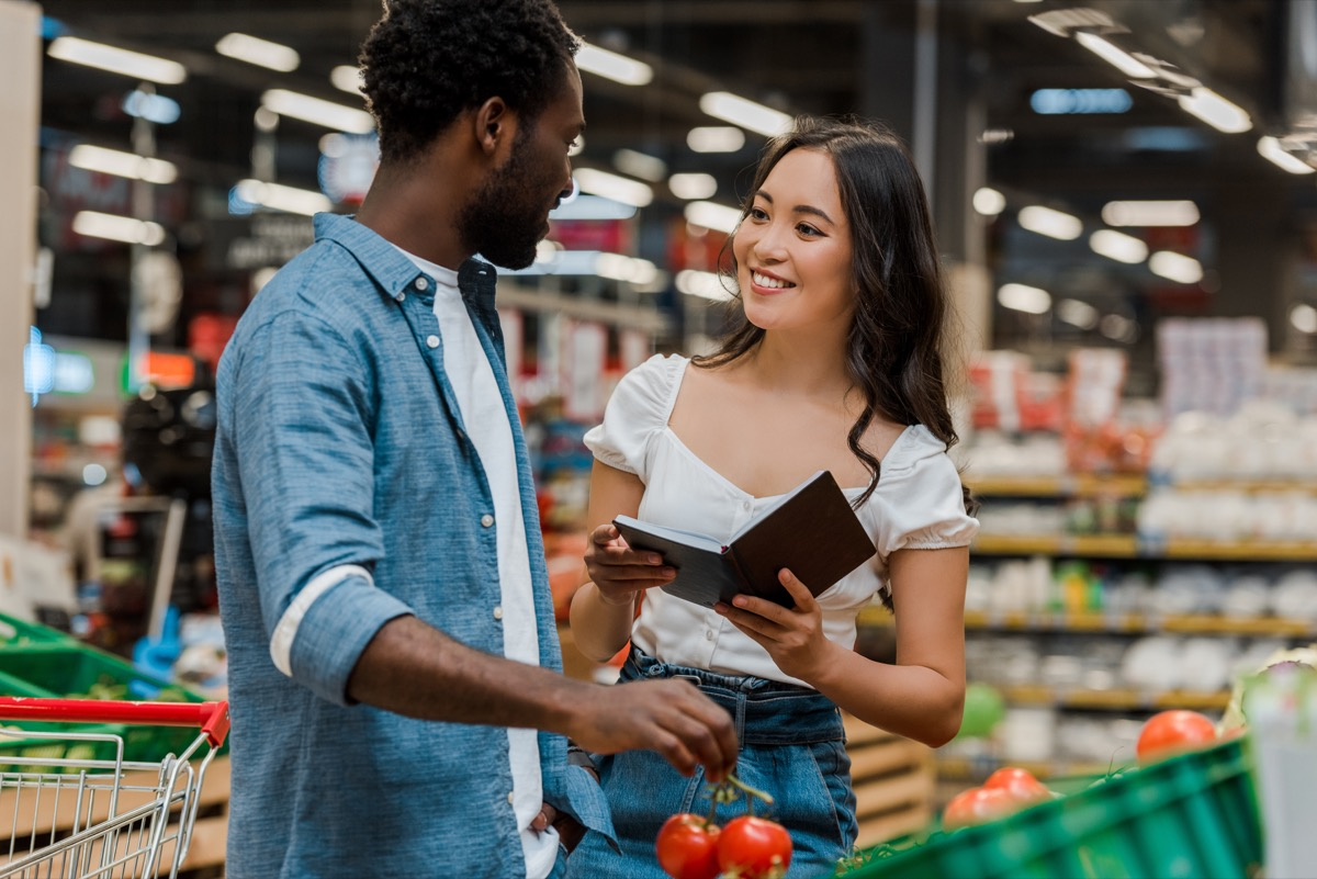 young black man talking to asian woman in grocery store
