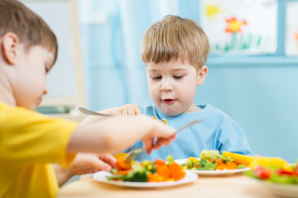 two white male toddlers eating vegetables