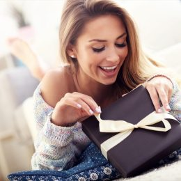 young white woman opening gift box