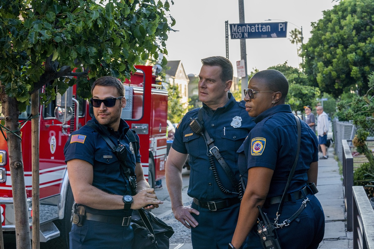 the cast of 9-1-1 standing on a street in front of a firetruck