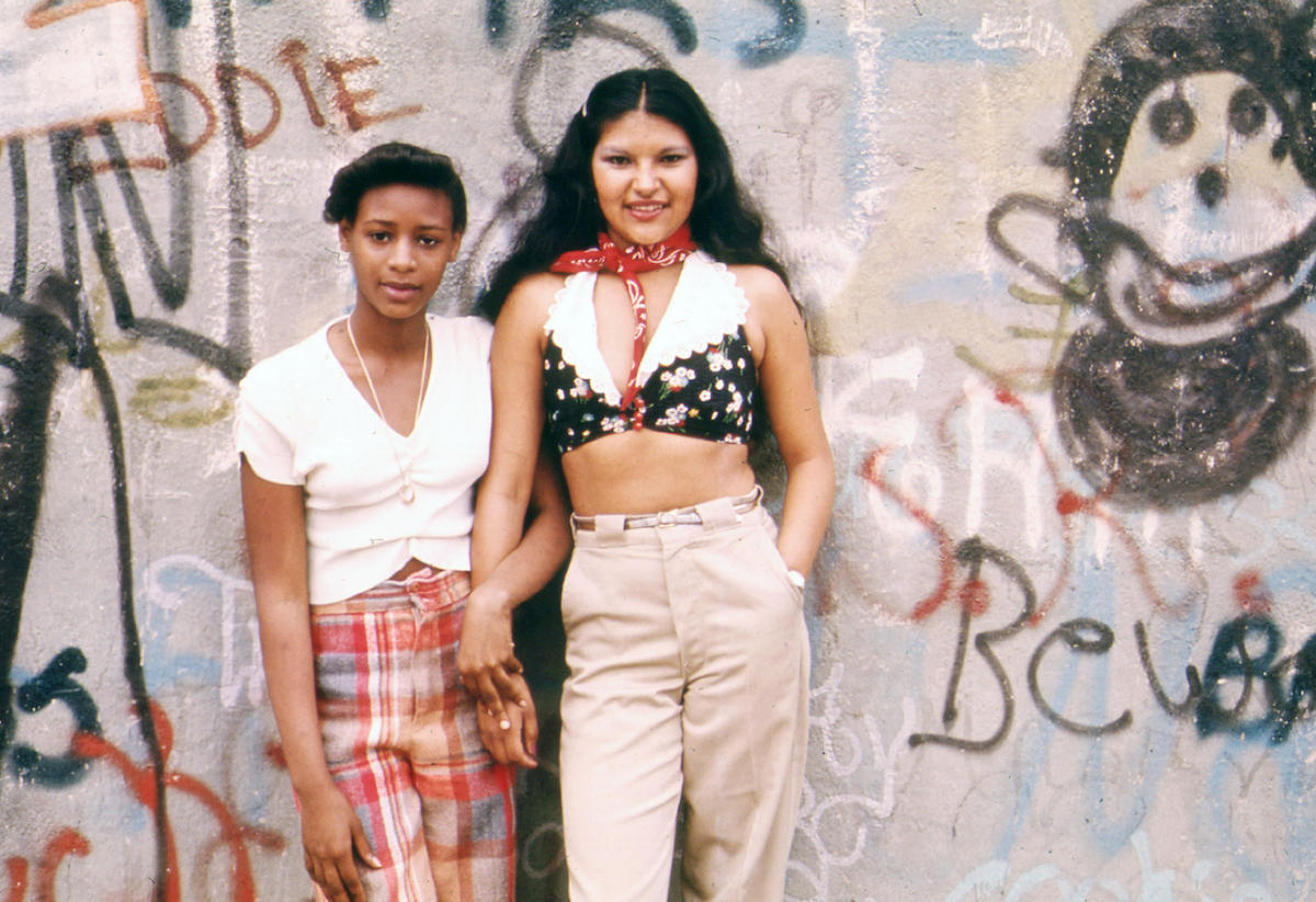Two teen women Pose in Front of a Wall of Graffiti in Lynch Park in Brooklyn, New York City in June 1974