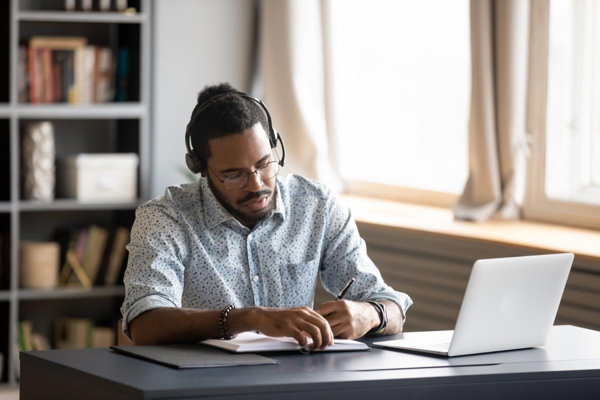 30-something black man working from home office wearing headphones
