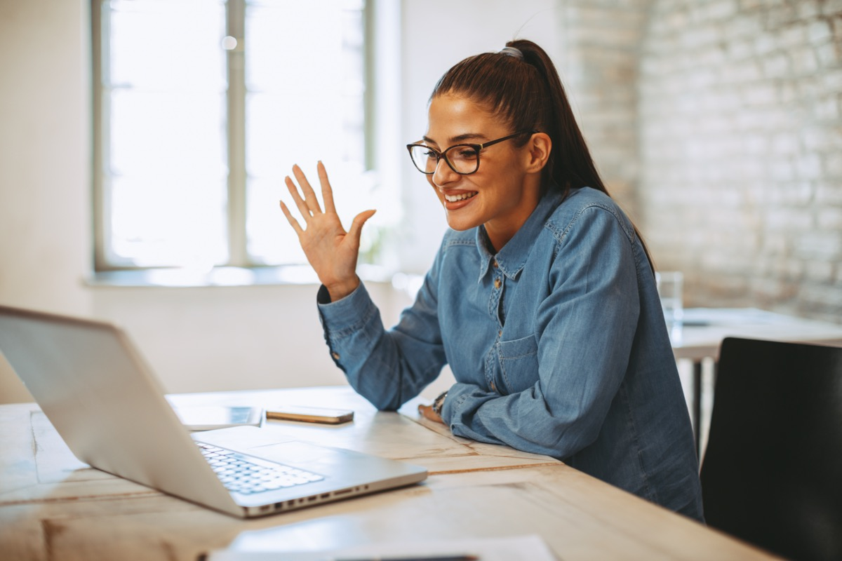 young woman in glasses waving to her laptop