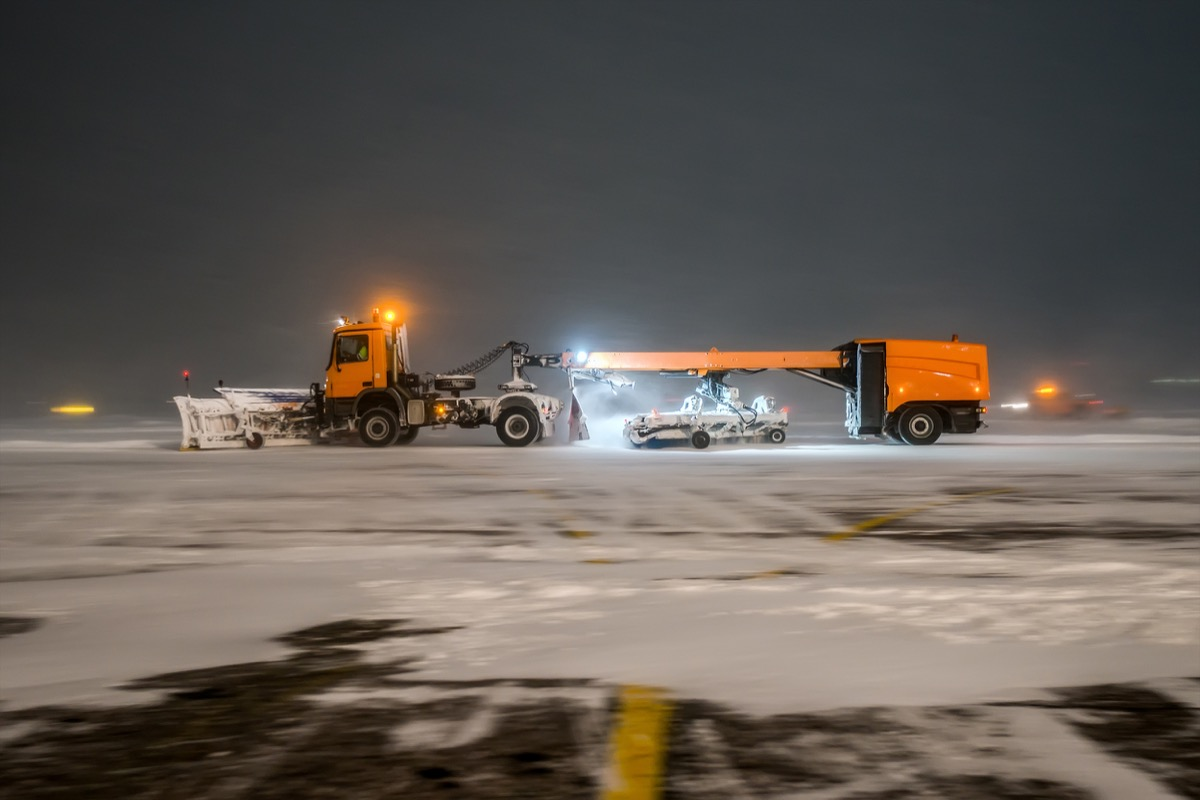 orange jet sweeper cleaning snow on airport ground