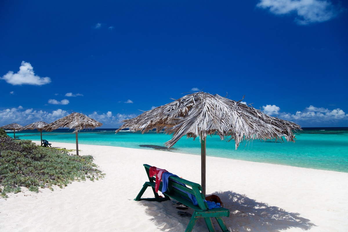 benches under cabana umbrellas on a white sand beach in Anegada, British Virgin Islands