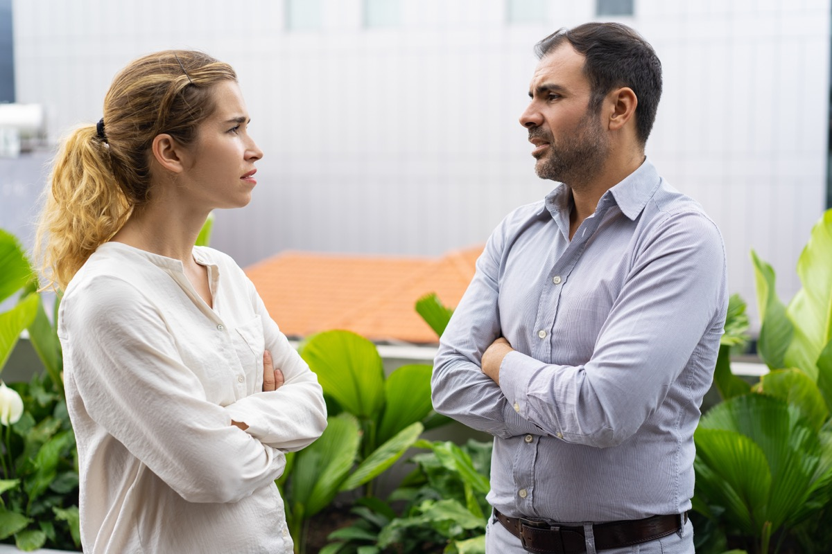 angry man and woman with crossed arms talking