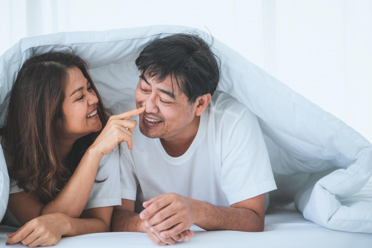 senior asian woman smiling with senior asian man underneath white comforter