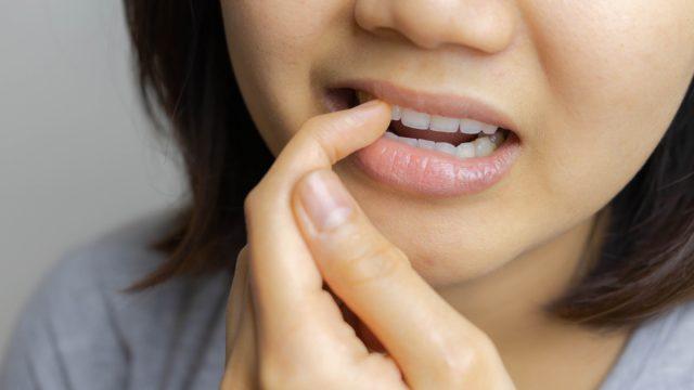 Asian woman picking teeth
