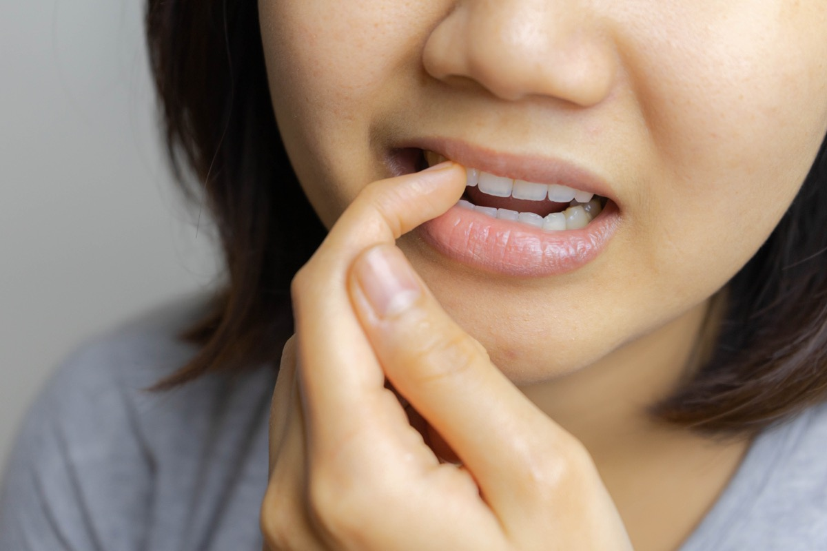 young asian woman picking teeth