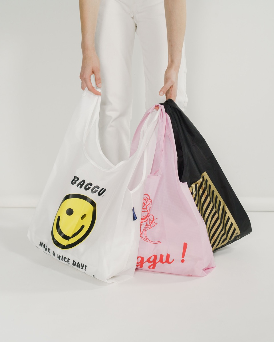 white hands holding reusable shopping bags