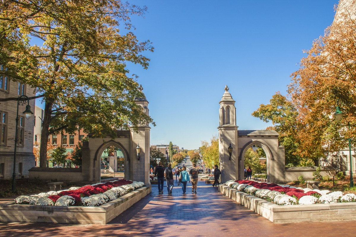 University of Indiana - Family walks with college student out main gates of campus down into the town during Fall Break weekend