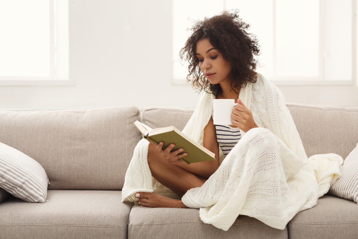 Girl reading a book on her couch with a mug