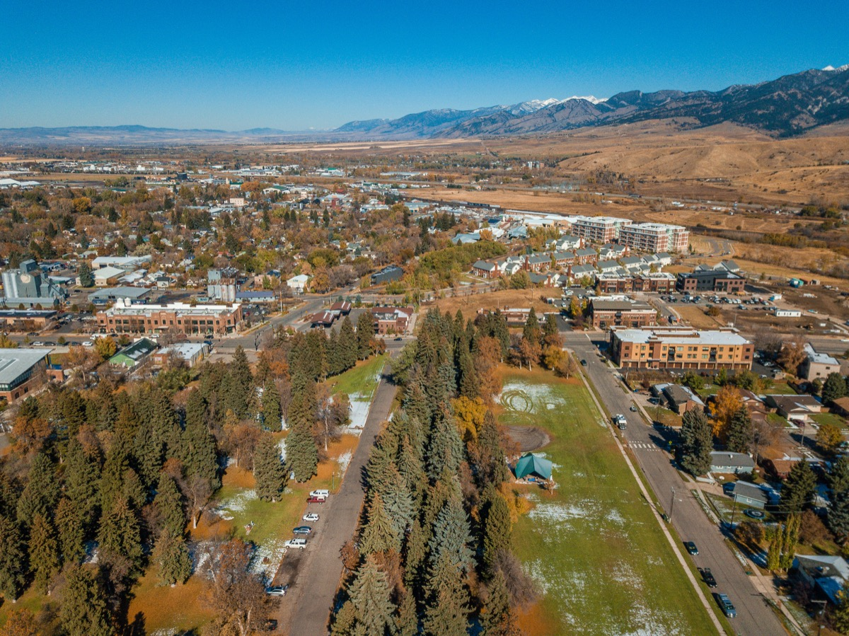 An aerial view of the brightly colored autumn trees in Lindley Park and a view of downtown Bozeman, Montana in Fall.