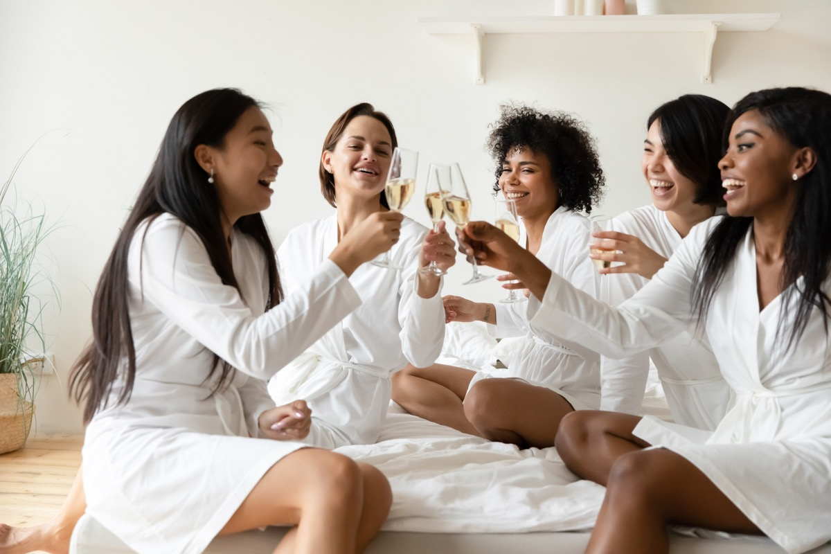 bridesmaids wearing a bunch of robes and cheering with champagne