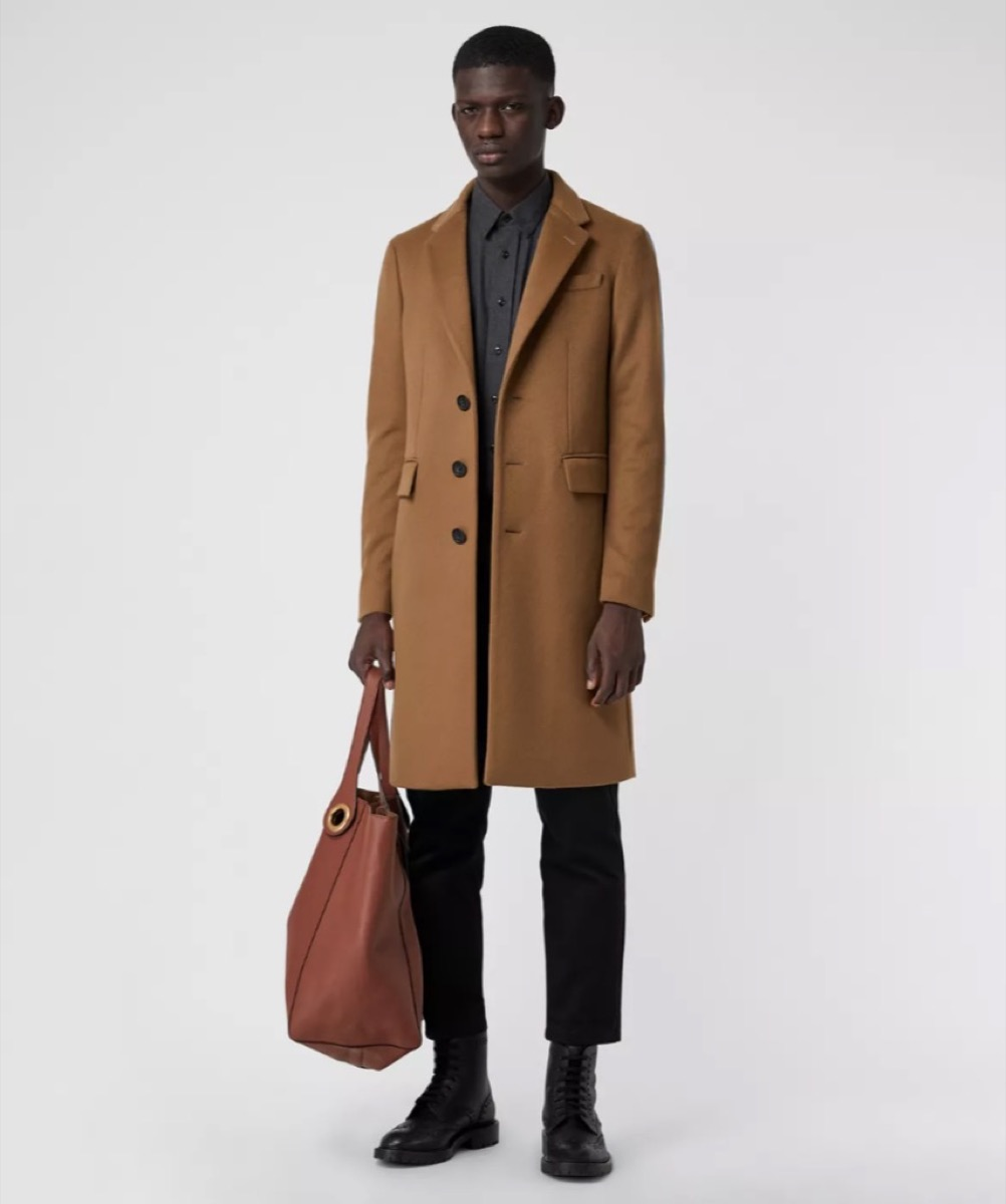 young black man in camel coat holding brown leather bag