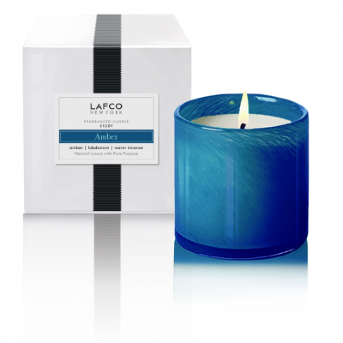 scented candle in blue glass jar with white box next to it
