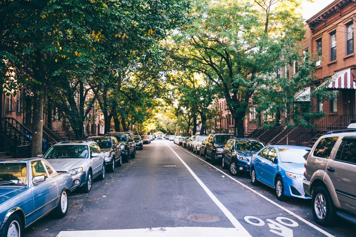 street with cars parked alongside in front of houses