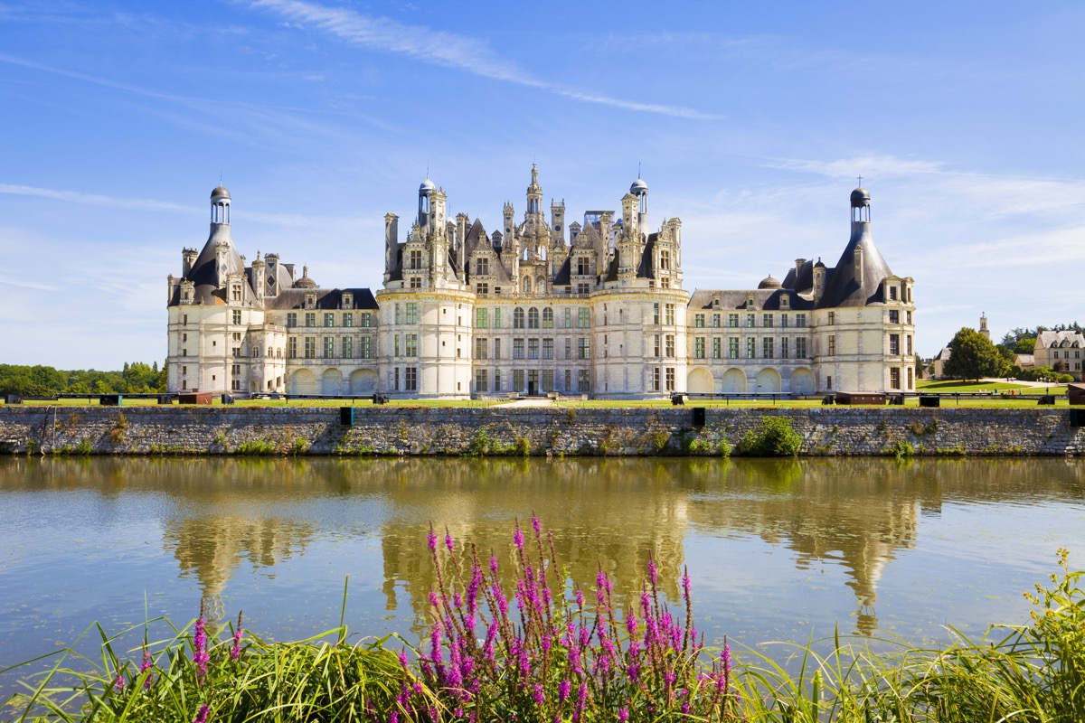 Great panoramic of Chambord Chateau reflected in the canal in a summer day with blue sky.