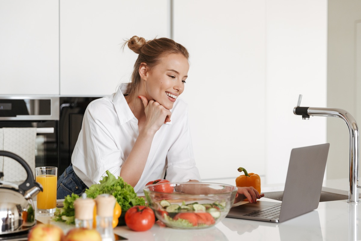 Woman cooking in kitchen with her laptop