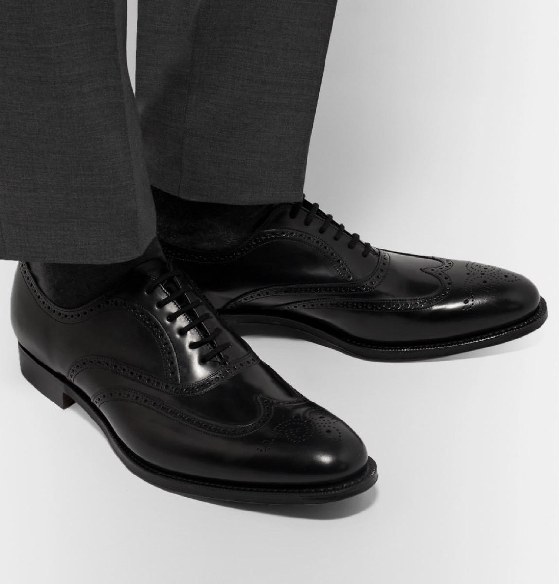 man wearing gray pants and black shiny shoes