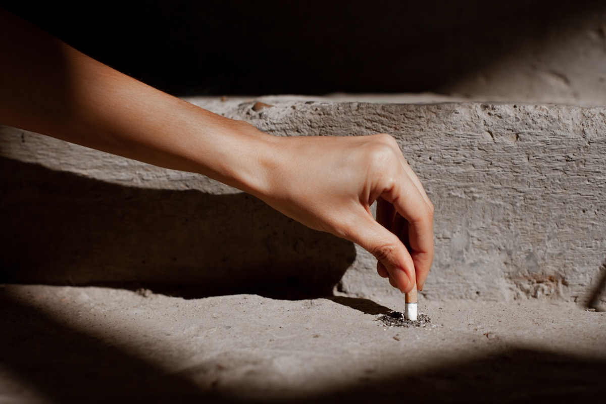 Person putting cigarette out