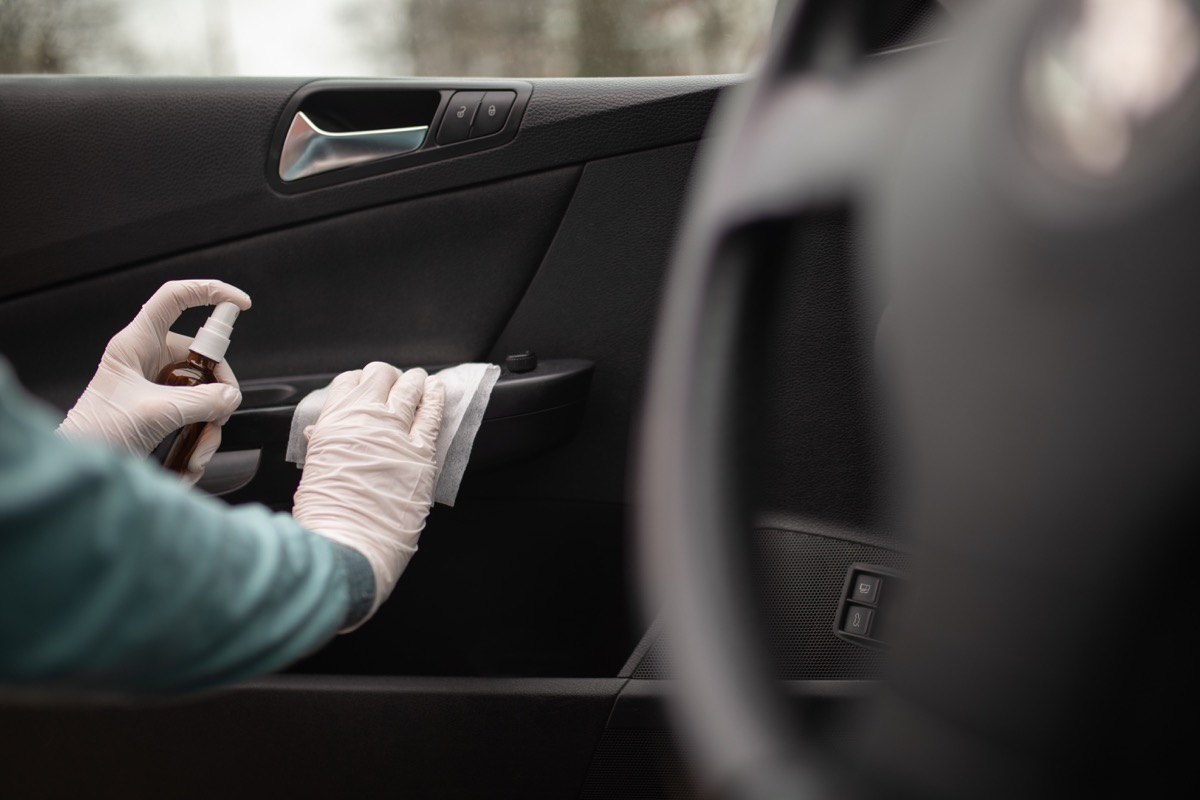 Person disinfecting and cleaning car interior with antiseptic liquid and wet disinfection wipes. Door handle is one of dirtiest parts in car and can contains viruses and bacteria.
