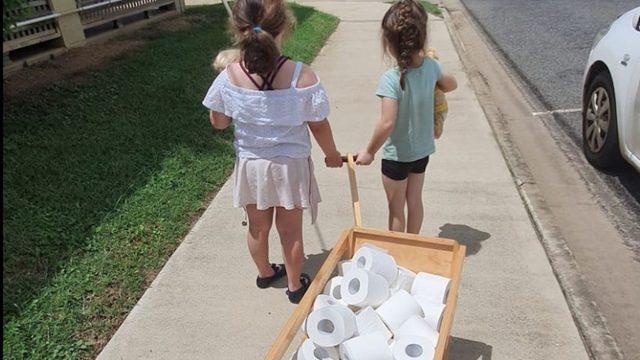 two girls pulling wagon of toilet paper, bringing it to elderly amid coronavirus panic