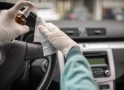 Person disinfecting and cleaning car interior with antiseptic liquid and wet disinfection wipes. Steering wheel is one of dirtiest parts in car and can contains viruses and bacteria.