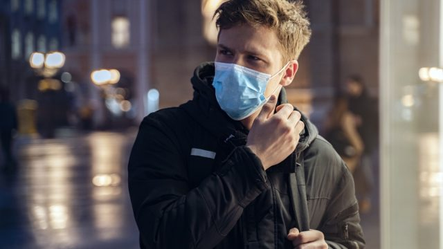 Blonde European teen with protective mask in the city