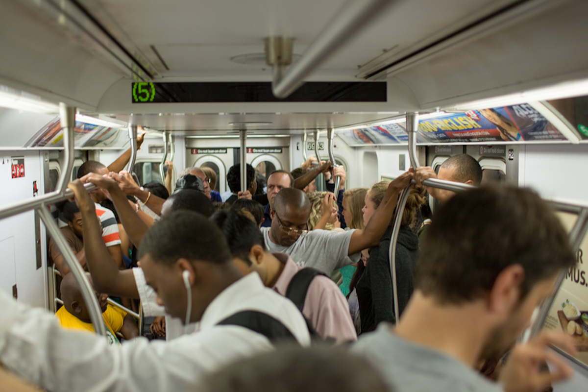 crowded new york city subway shows people holding on to bar