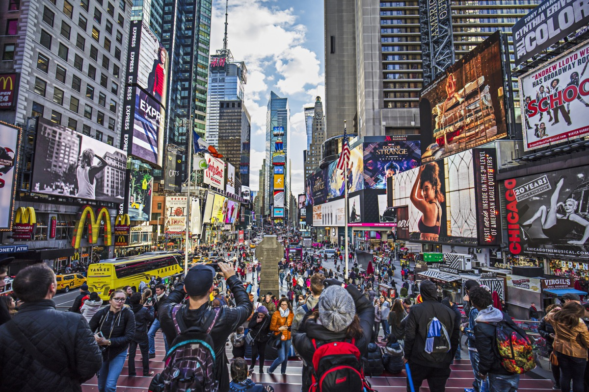 View of crowded Times Square in New York City. People are at major commercial intersection and neighborhood in Midtown Manhattan. Commercial signs are on buildings in city. Travel Locations.