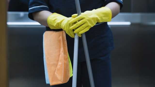 closeup of midsection of custodian's body, their hands are in gloves and they're holding a mop