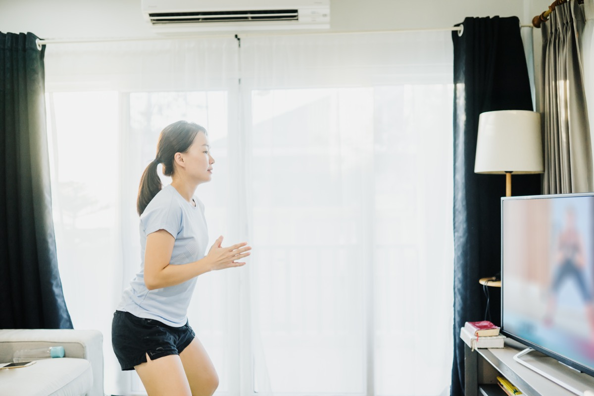 Woman doing at home dance lesson on tv in living room