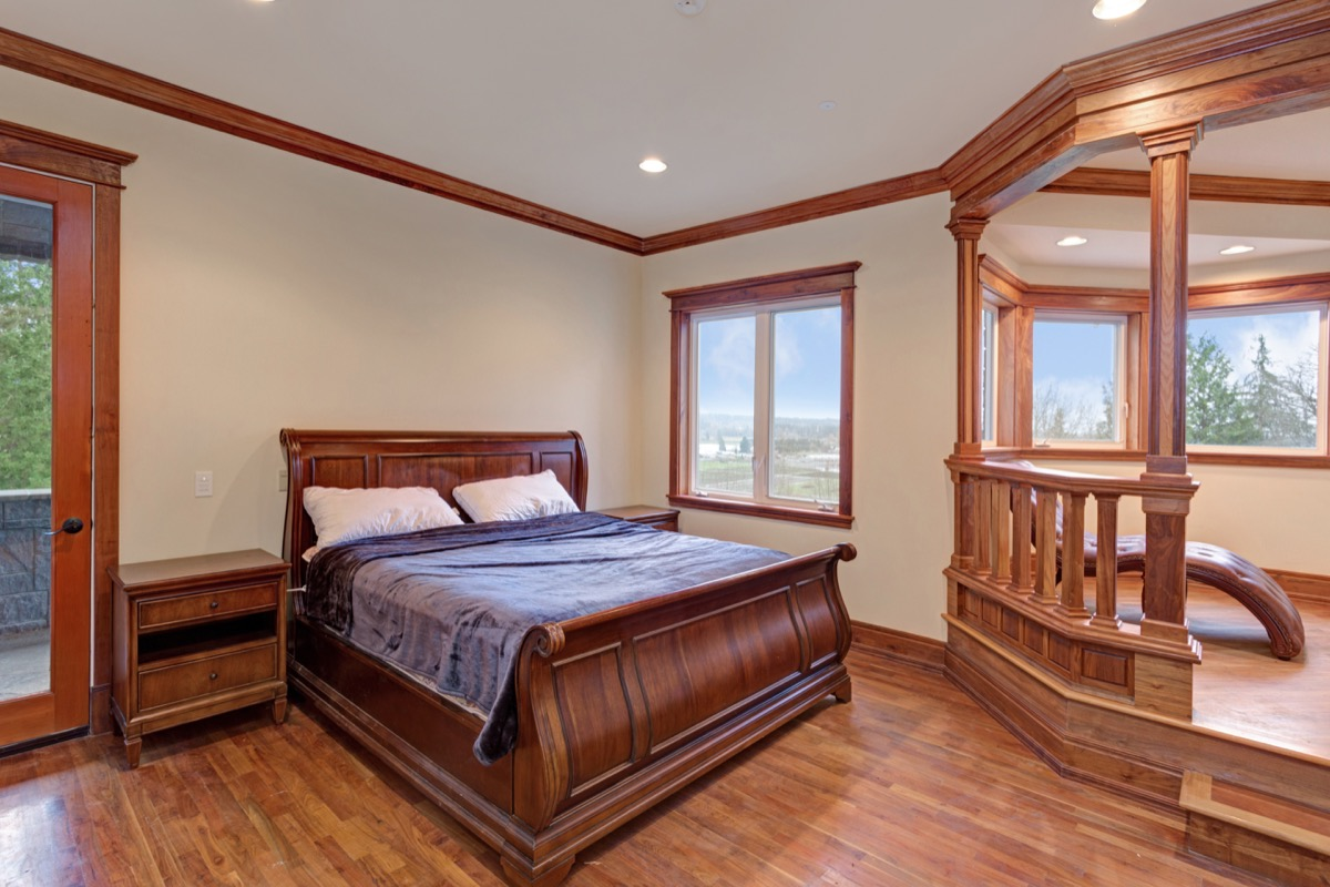 dark wood sleigh bed and chaise in large bedroom