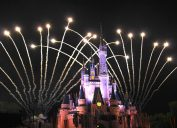 Disney castle at night with fireworks behind it