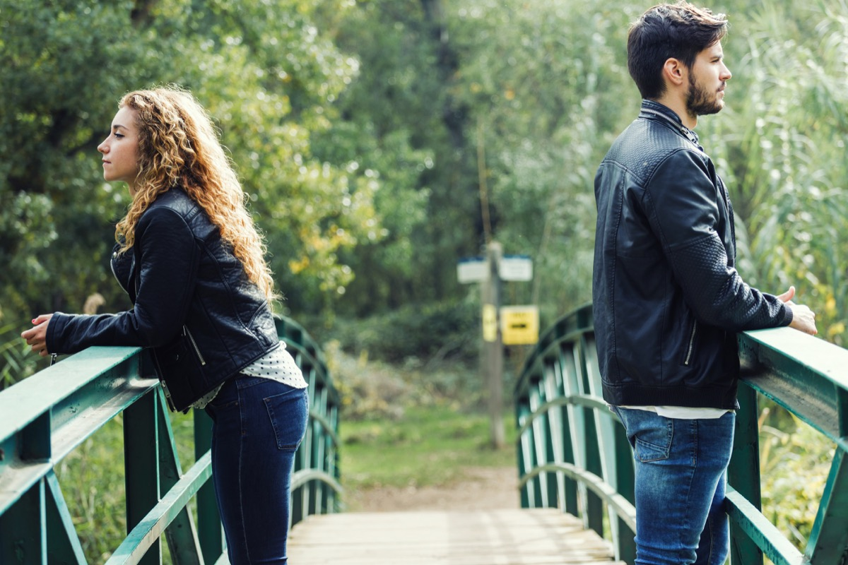 Couple on a bridge keeping distance between them