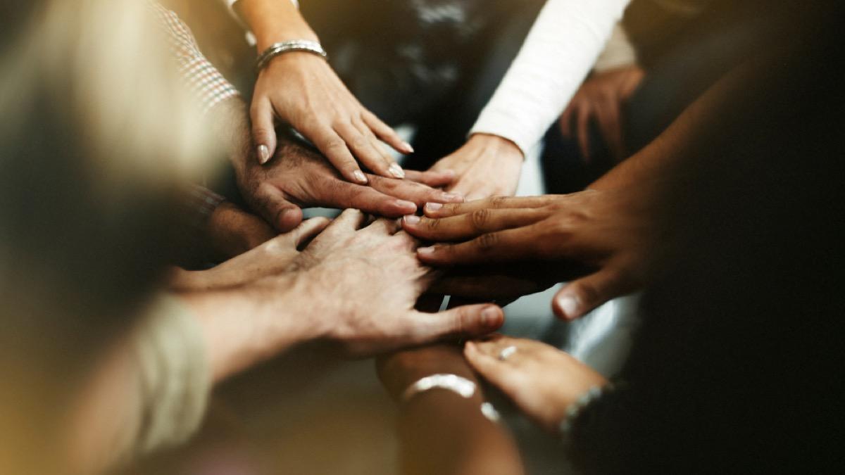 diverse hands in huddle