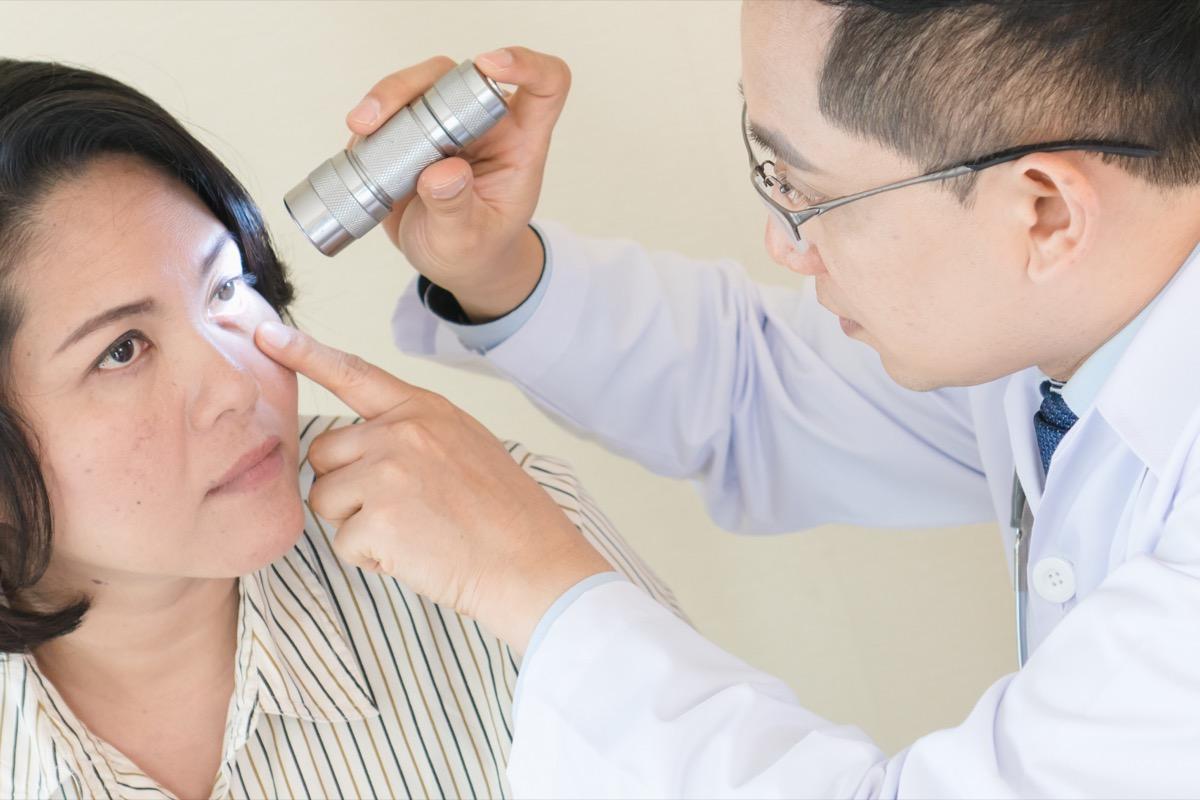 asian doctor examining woman's eye with flashlight