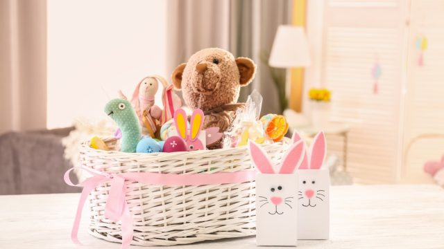 large white easter basket with pink bow on white table