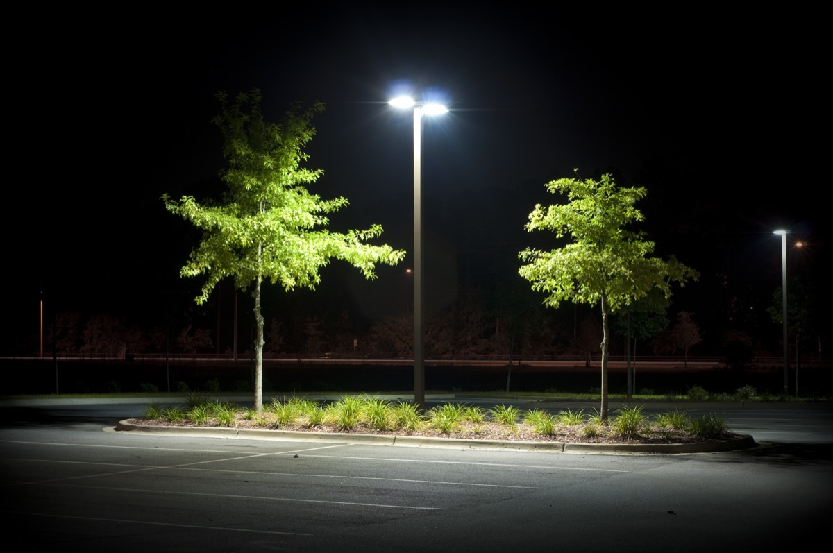 empty parking with one light pole at night