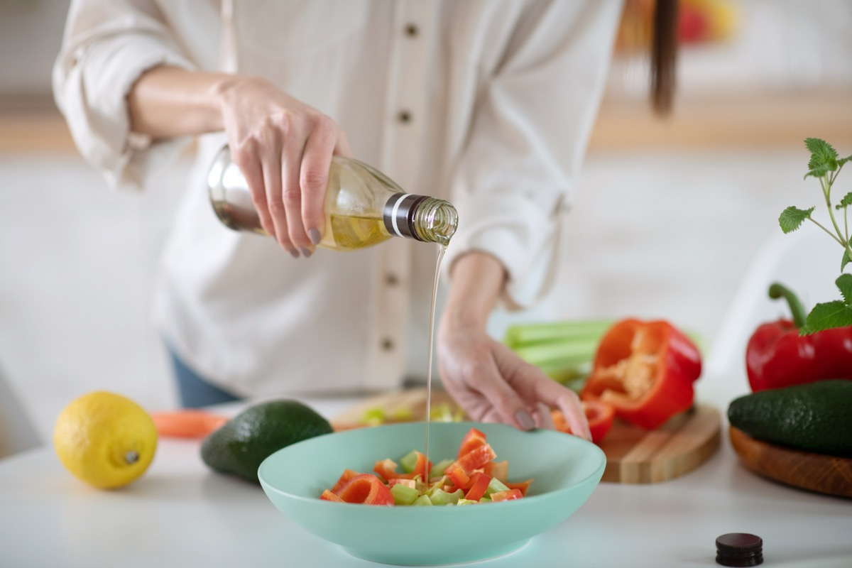Woman pouring olive oil on salad with avocado