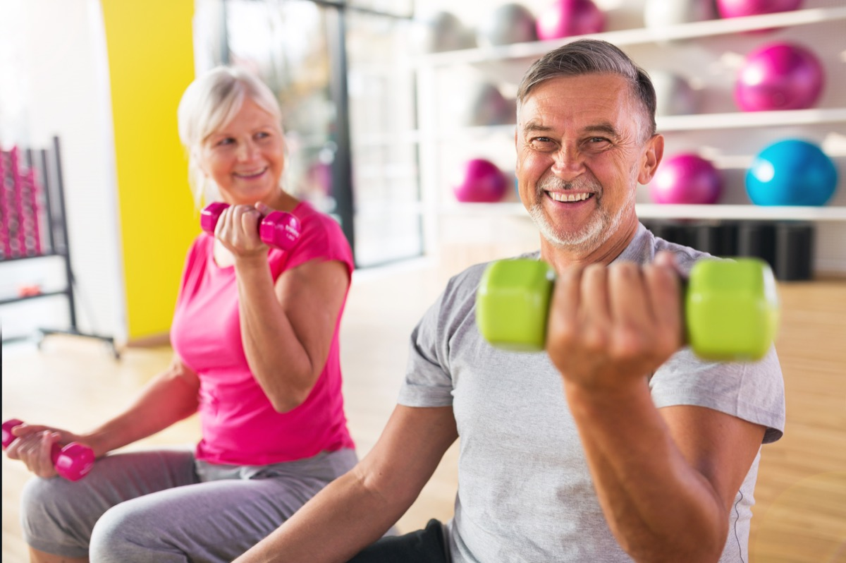 Older couple exercising lifting weights