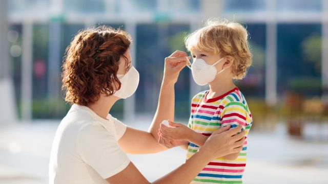 Mother putting a face mask on her child's face