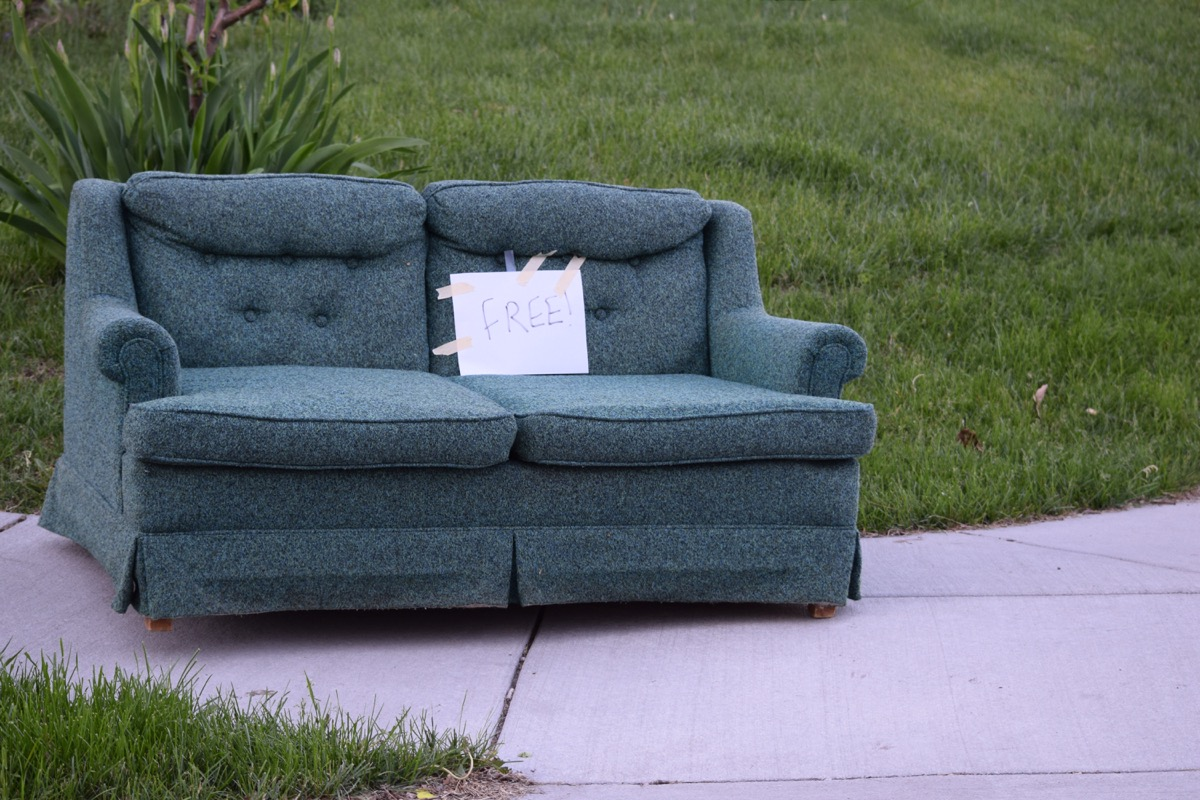 sofa placed on the sidewalk with a sign marking it free for pick up