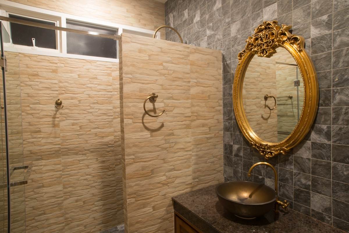 ornate gold mirror hung in bathroom