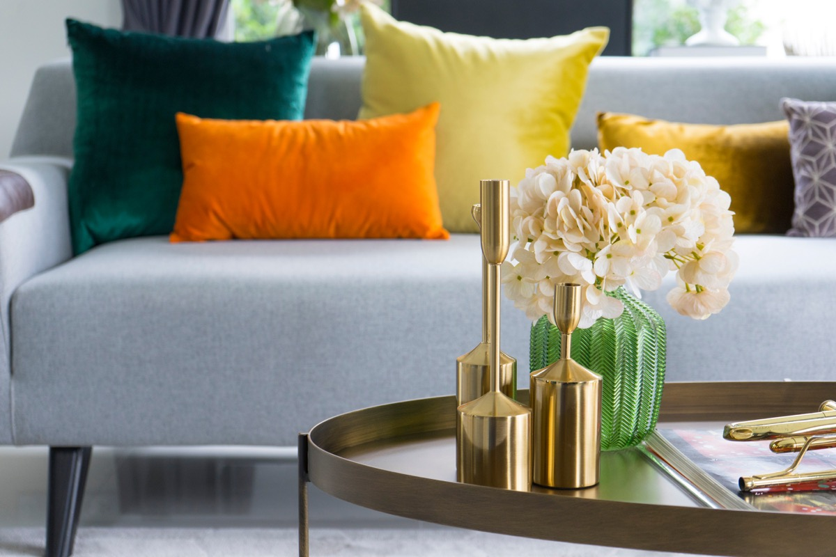 gold vases and flowers on table in front of sofa
