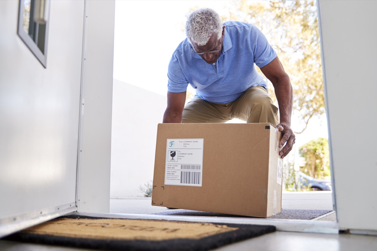 Senior Man Coming Back To Home Delivery In Cardboard Box Outside Front Door