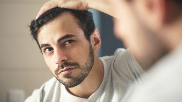 Man looking at his hair